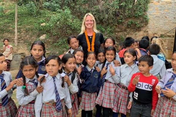Sally Darlin pictured with schoolchildren in Nepal